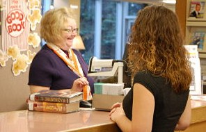 Library employee checking books out to a customer